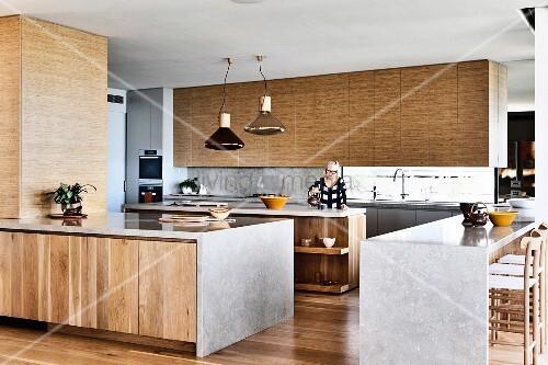 k chenbl cke mit holzfronten und kalkstein arbeitsplatte in offener k che frau im hintergrund. Black Bedroom Furniture Sets. Home Design Ideas