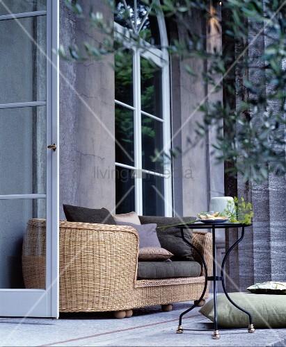ovales rattansofa und ein metalltisch vor klassischem haus. Black Bedroom Furniture Sets. Home Design Ideas