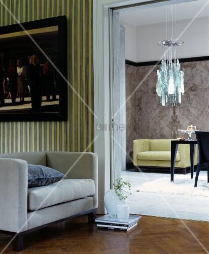 kleines sofa vor offenem durchgang ins esszimmer mit moderner leuchte bild kaufen living4media. Black Bedroom Furniture Sets. Home Design Ideas