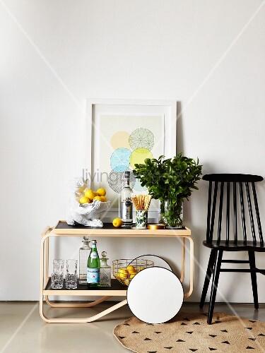 klassiker servierwagen mit zitronen getr nkeflaschen bl tterzweigen neben schwarzem stuhl. Black Bedroom Furniture Sets. Home Design Ideas