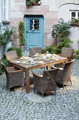 innenhof mit gedecktem tisch vor blauer eingangst r bild. Black Bedroom Furniture Sets. Home Design Ideas