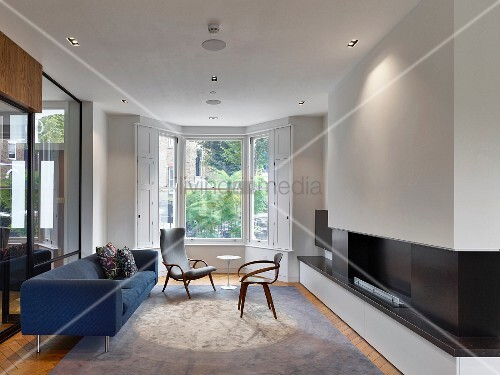 Blue Sofa Fireplace And Bay Window In Living Room With