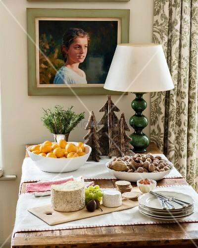 rustikaler tisch mit k seplatte und schalen mit mandarinen. Black Bedroom Furniture Sets. Home Design Ideas