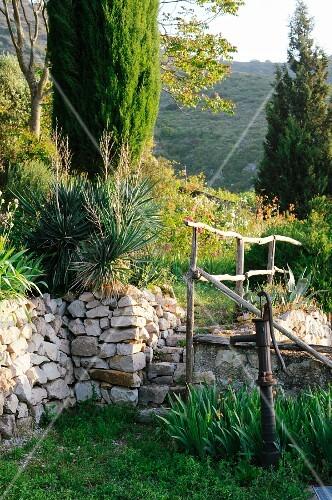 Wasserpumpe im mediterranen garten mit steinmauer bild for Garten wasserpumpe