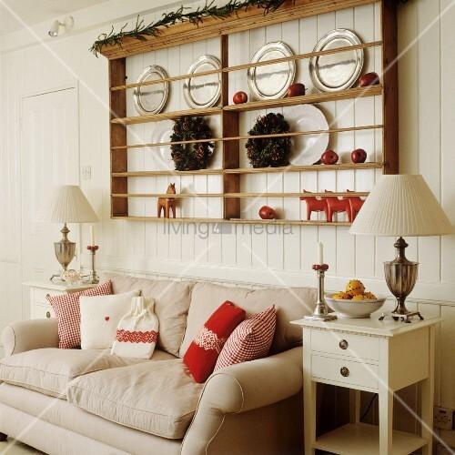 tellerregal an bretterwand ber dem sofa mit roten kissen bild kaufen living4media. Black Bedroom Furniture Sets. Home Design Ideas