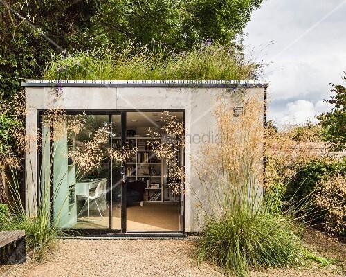 kubischer bungalow im garten mit glasfront zum wohnzimmer bild kaufen living4media. Black Bedroom Furniture Sets. Home Design Ideas