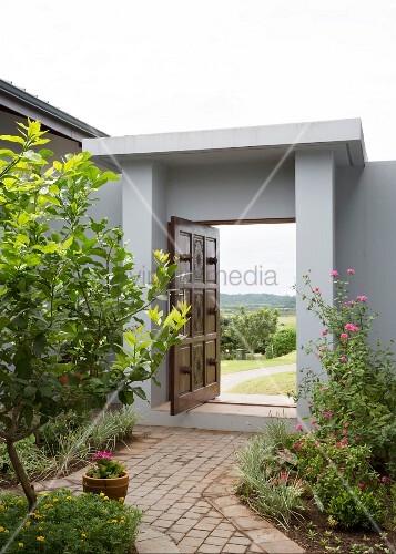 graue moderne gartenmauer mit ge ffnetem holzportal bild kaufen living4media. Black Bedroom Furniture Sets. Home Design Ideas