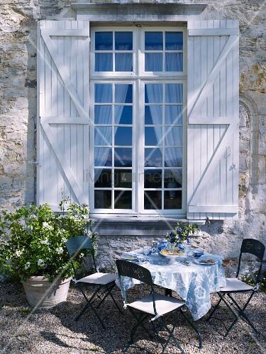 gedeckter gartentisch vor einem sprossenfenster mit fensterl den bild kaufen living4media. Black Bedroom Furniture Sets. Home Design Ideas