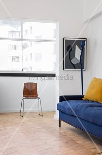 Blaues polstersofa stehlampe und stuhl vor fenster im for Couch vor fenster