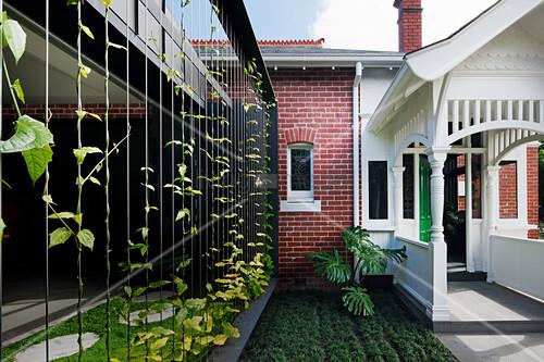 blick auf haus mit backsteinfassade windfang aus weiss. Black Bedroom Furniture Sets. Home Design Ideas