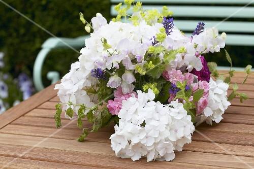 sommerlicher blumenstrauss mit hortensien auf gartentisch bild kaufen living4media. Black Bedroom Furniture Sets. Home Design Ideas