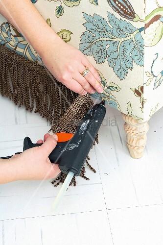 polsterhocker selber bauen fransen an polsterm bel mit klebepistole anbringen bild kaufen. Black Bedroom Furniture Sets. Home Design Ideas
