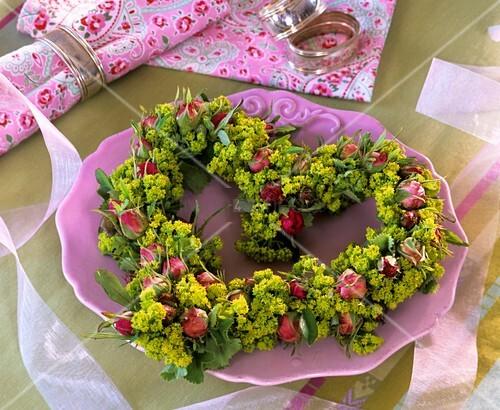 Herzförmiges Blumengesteck aus Rosen und Frauenmantel ...