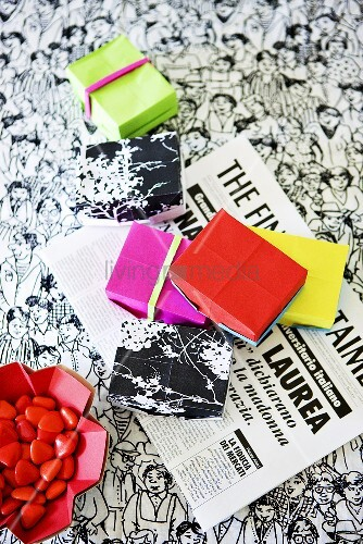 kleine schachteln mit bonbons auf italienischer zeitung bild kaufen living4media. Black Bedroom Furniture Sets. Home Design Ideas