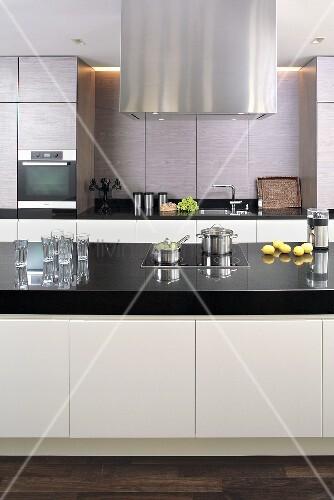 ausschnitt einer designer k che mit edelstahldunstabzugshaube ber kochinsel bild kaufen. Black Bedroom Furniture Sets. Home Design Ideas