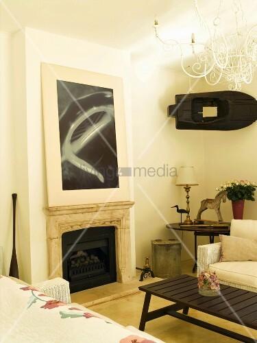 wohnraumecke mit zeitgen ssischem bild ber dem kamin und kleinem aufgeh ngten boot an der wand. Black Bedroom Furniture Sets. Home Design Ideas