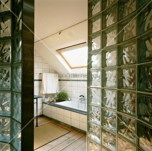 blick durch wand aus glasbausteinen in bad ensuite mit dachfl chenfenster ber der eingebauten. Black Bedroom Furniture Sets. Home Design Ideas