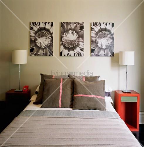 doppelbett mit zierkissen flankiert von roten nachtk stchen mit tischlampen und schwarzweiss. Black Bedroom Furniture Sets. Home Design Ideas