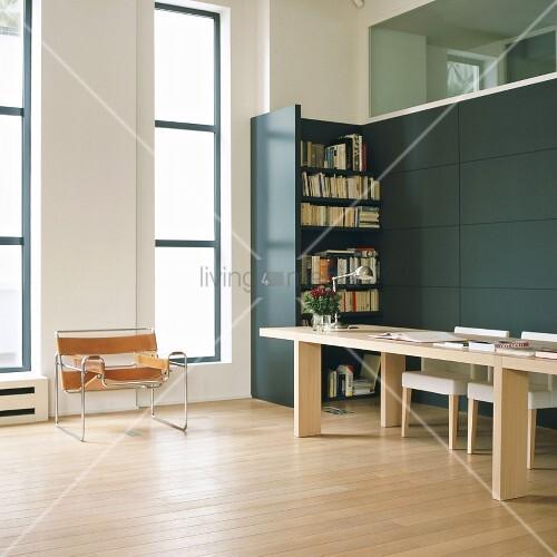 grosser arbeitstisch vor modernem einbauregal und 20er jahre stahlrohr sessel in loft wohnung. Black Bedroom Furniture Sets. Home Design Ideas