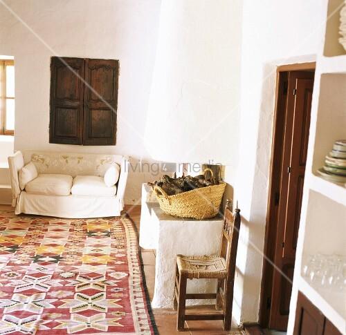 Rustikaler, weiss verputzter Wohnraum mit Teppich im