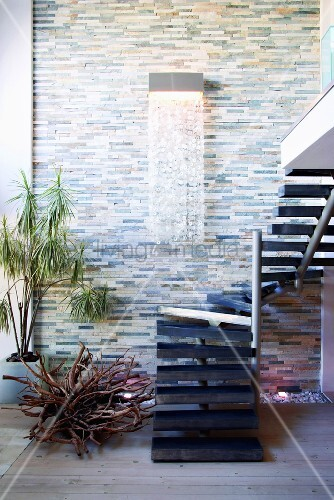 wandleuchte mit kristallvorhang an natursteinwand und gewendelte treppe auf eine wohnraumgalerie. Black Bedroom Furniture Sets. Home Design Ideas