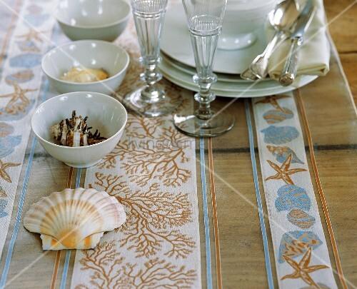 tisch mit geschirr und muscheln als deko bild kaufen living4media. Black Bedroom Furniture Sets. Home Design Ideas
