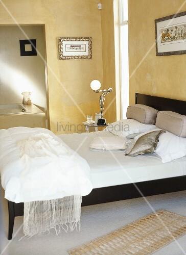 gelbes schlafzimmer mit doppelbett kunstvoller nachttischlampe und bad ensuite bild kaufen. Black Bedroom Furniture Sets. Home Design Ideas