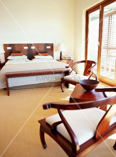 modernes schlafzimmer mit doppelett bank und bequemen st hlen aus edelholz bild kaufen. Black Bedroom Furniture Sets. Home Design Ideas
