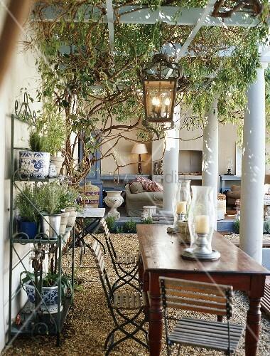 Holztisch mit klappst hlen auf berdachter terrasse mit pergola s ulen und einem metallregal - Holztisch terrasse ...