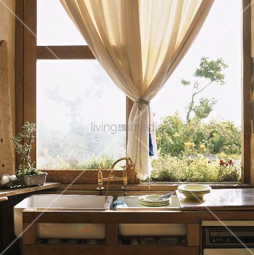 sp lbecken und geschirr vor offenem fenster bild kaufen living4media. Black Bedroom Furniture Sets. Home Design Ideas