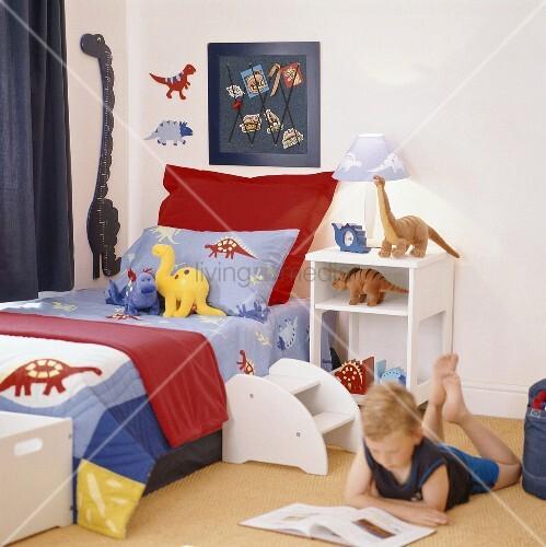 junge liest ein buch auf dem boden seines kinderzimmers. Black Bedroom Furniture Sets. Home Design Ideas