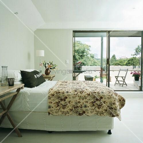 doppelbett und gebl mte tagesdecke vor schiebefenster mit blick auf den balkon bild kaufen. Black Bedroom Furniture Sets. Home Design Ideas