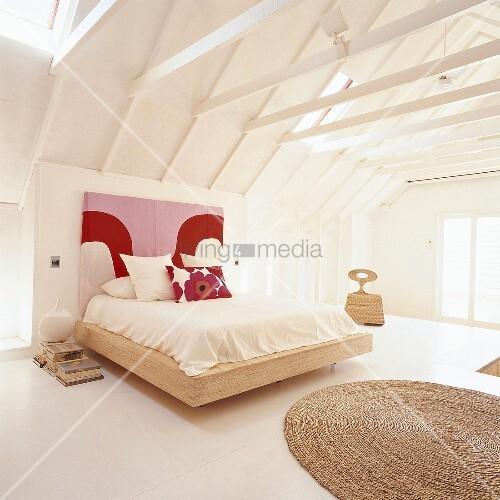 ein doppelbett mit buntem kopfteil unter offener. Black Bedroom Furniture Sets. Home Design Ideas