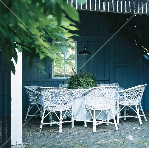 berdachte terrasse mit runden tisch und rattansesseln bild kaufen living4media. Black Bedroom Furniture Sets. Home Design Ideas
