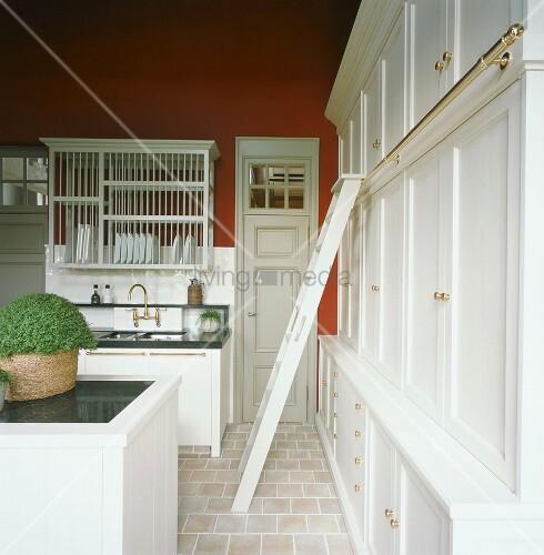 traditionelle k che mit einer leiter zu den oberen k chenschr nken und mit einem k chenblock. Black Bedroom Furniture Sets. Home Design Ideas