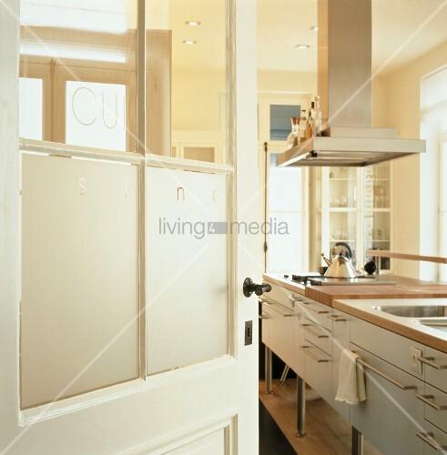 blick durch eine offene t r in einer k che mit edelstahl dunstabzugshaube ber kochinsel bild. Black Bedroom Furniture Sets. Home Design Ideas