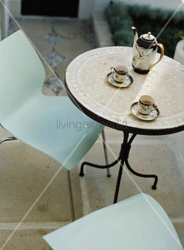 runder metalltisch mit mosaikplatte und asiatischem teeset im garten bild kaufen living4media. Black Bedroom Furniture Sets. Home Design Ideas