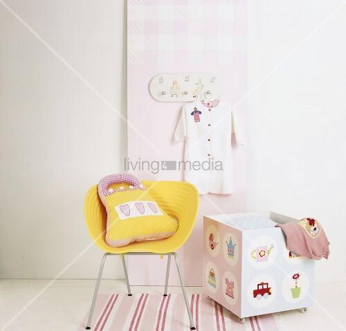 ausschnitt eines gelben schalenstuhls und bunten kiste auf rollen bild kaufen living4media. Black Bedroom Furniture Sets. Home Design Ideas