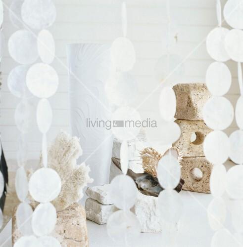 gestapelte steine und dekorationsartikel hinter einem pailletten vorhang bild kaufen. Black Bedroom Furniture Sets. Home Design Ideas