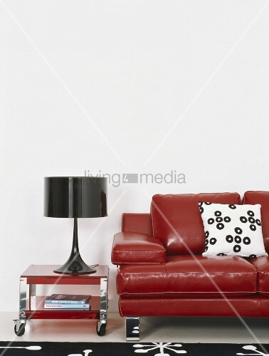 eine rote ledercouch neben schwarzer tischlampe auf einem roten couchtisch auf rollen bild. Black Bedroom Furniture Sets. Home Design Ideas