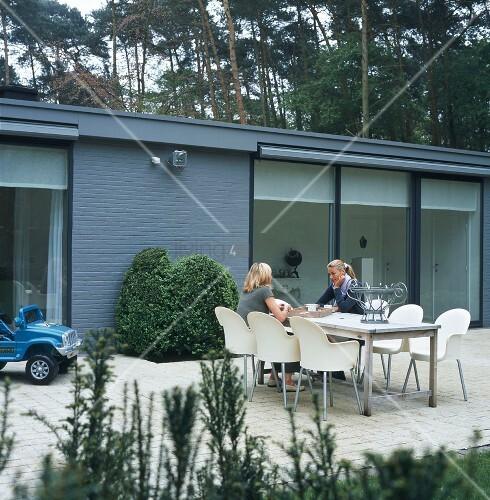 zwei frauen sitzen am tisch auf der terrasse bild kaufen living4media. Black Bedroom Furniture Sets. Home Design Ideas