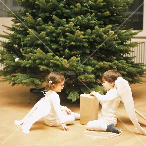 m dchen und junge packen weihnachtsgeschenk aus bild. Black Bedroom Furniture Sets. Home Design Ideas