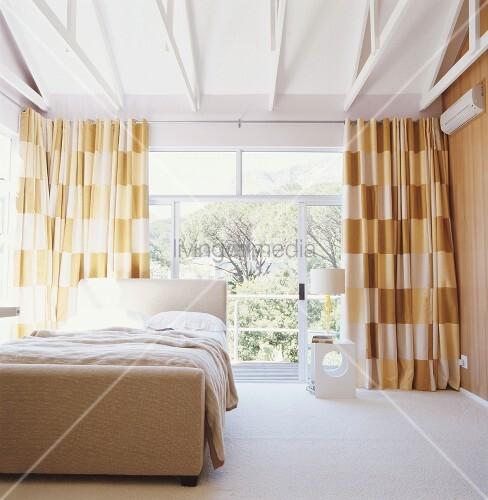 schlafzimmer in braunt nen mit verglaster front und weisser holzbalkendecke bild kaufen. Black Bedroom Furniture Sets. Home Design Ideas