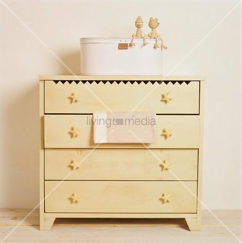 eine einfache gelbe holzkommode mit sternkn pfen an den. Black Bedroom Furniture Sets. Home Design Ideas