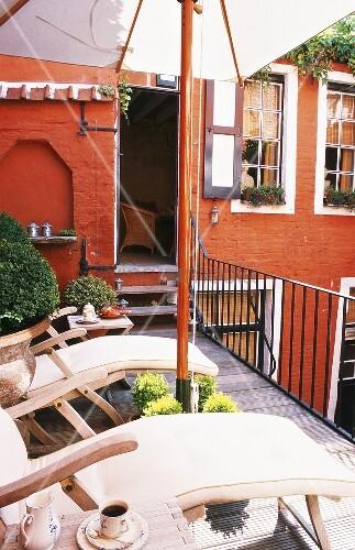 die dachterrasse des traditionellen backsteinhauses mit sonnenschirm und liegest hlen l dt zu. Black Bedroom Furniture Sets. Home Design Ideas