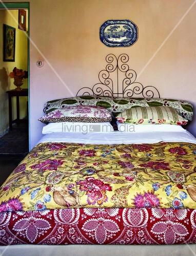 ein doppelbett mit bunt gemusterter bettw sche bild. Black Bedroom Furniture Sets. Home Design Ideas