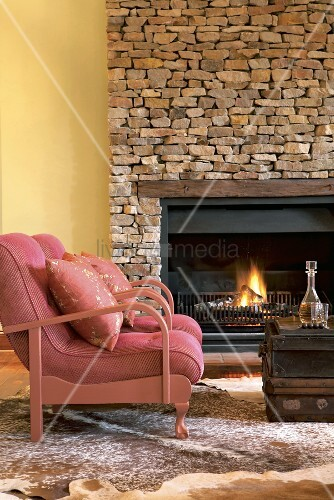 zwei rosa sessel und antike koffer vor einem kamin mit. Black Bedroom Furniture Sets. Home Design Ideas