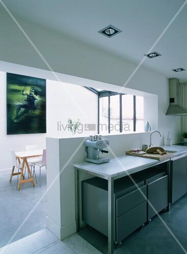 ein l f rmiger wanddurchbruch f hrt den blick von der k hlen k che in das helle esszimmer mit. Black Bedroom Furniture Sets. Home Design Ideas