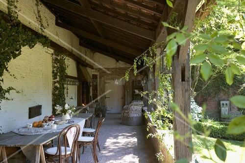 Einfacher holztisch und thonetst hle auf der rustikalen berdachten terrasse eines alten - Holztisch terrasse ...