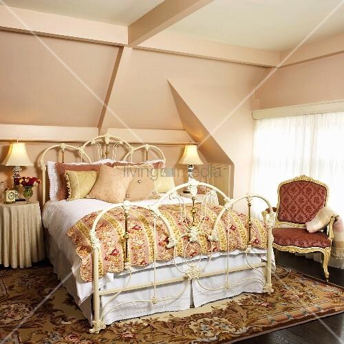 Schlafzimmer mit MetallDoppelbett, antikem Polsterstuhl